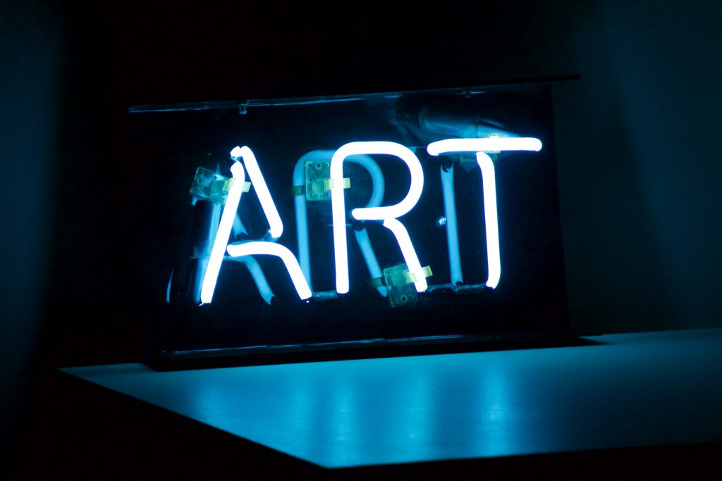 Photo of a neon sign that says art