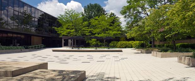 Color photograph depicting outdoor plaza. To the left is the school of art and design. The top and left are flanked by green trees.