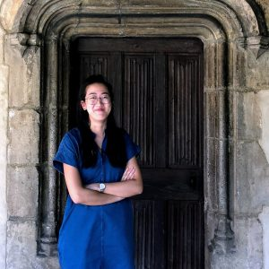 A woman in front of a wooden door in a stone setting.