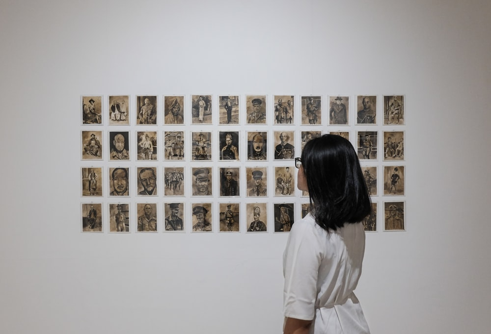 A person with long hair and glasses looking at a wall of drawings.