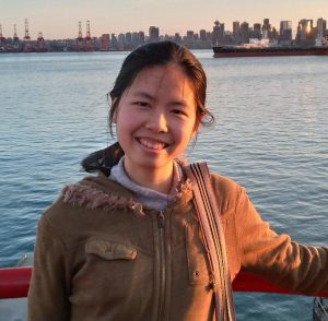 A phot of Eileen Chen standing in front of a skyline on a boat